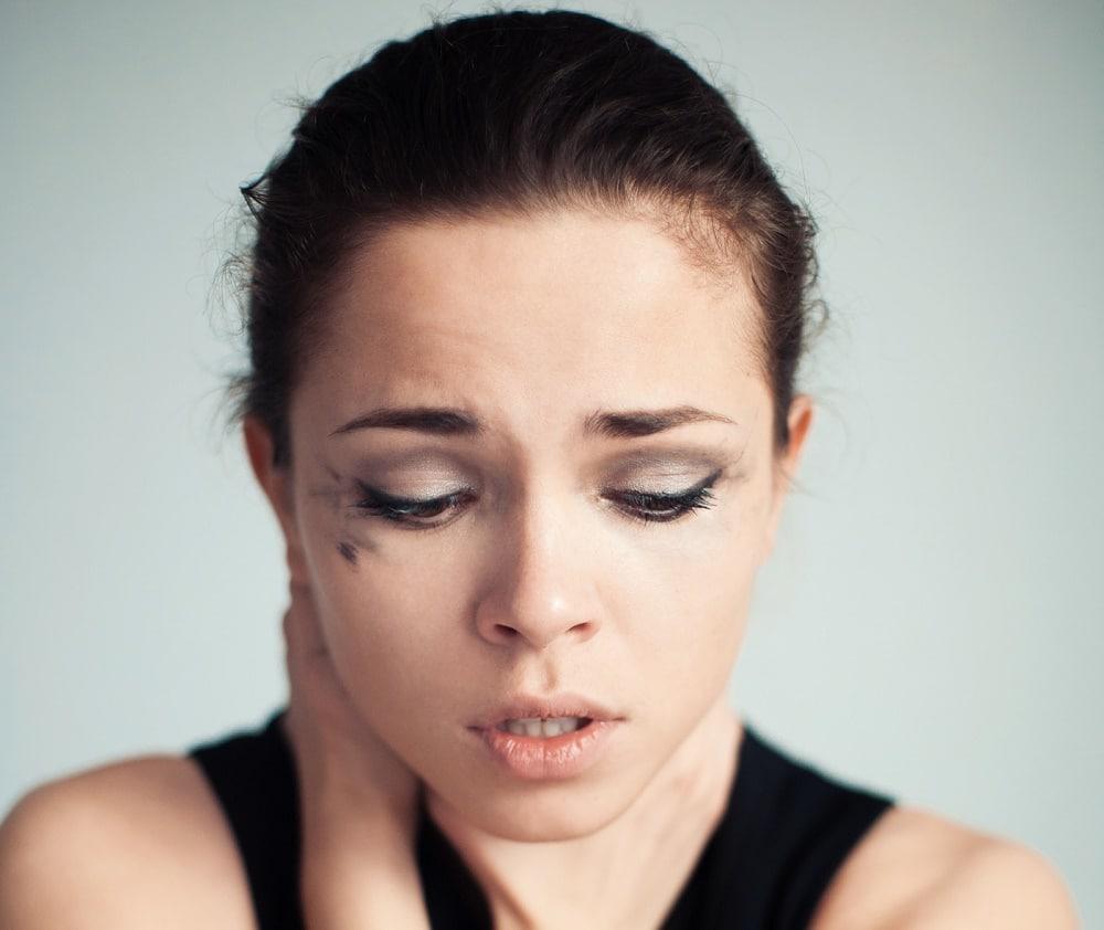 donna con respiro affannoso che si tocca la gola