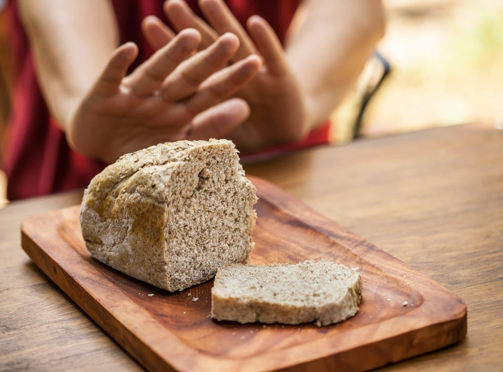 cos'è il glutine - fetta di pane su tagliere e mani di donna che fanno cenno per rifiutarlo
