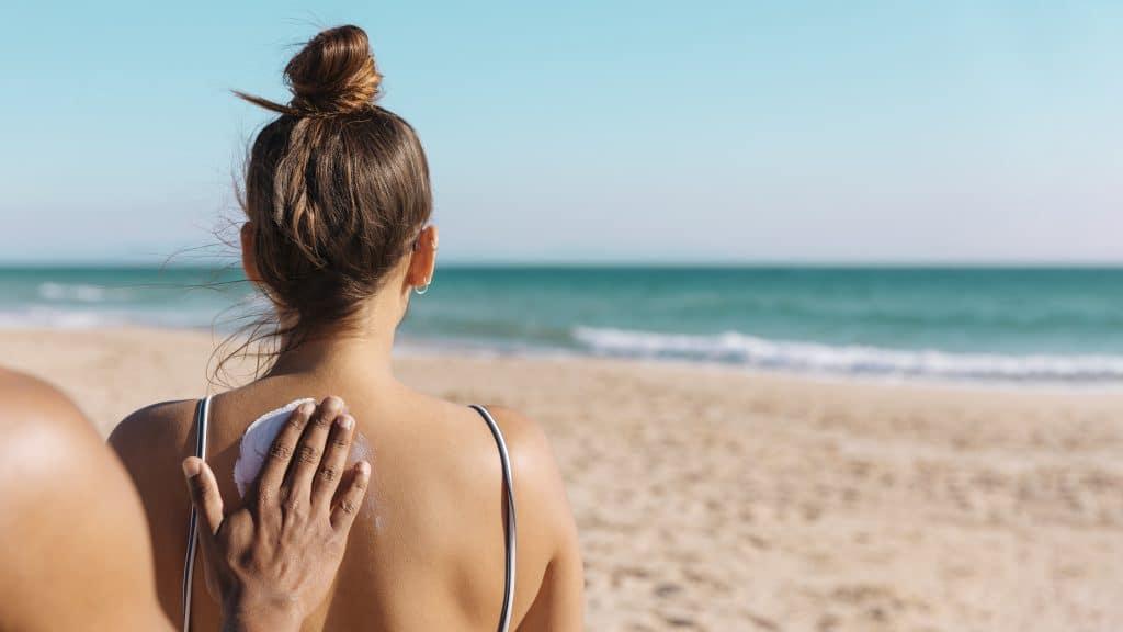 Donna che si fa spalmare la crema solare sulla schiena