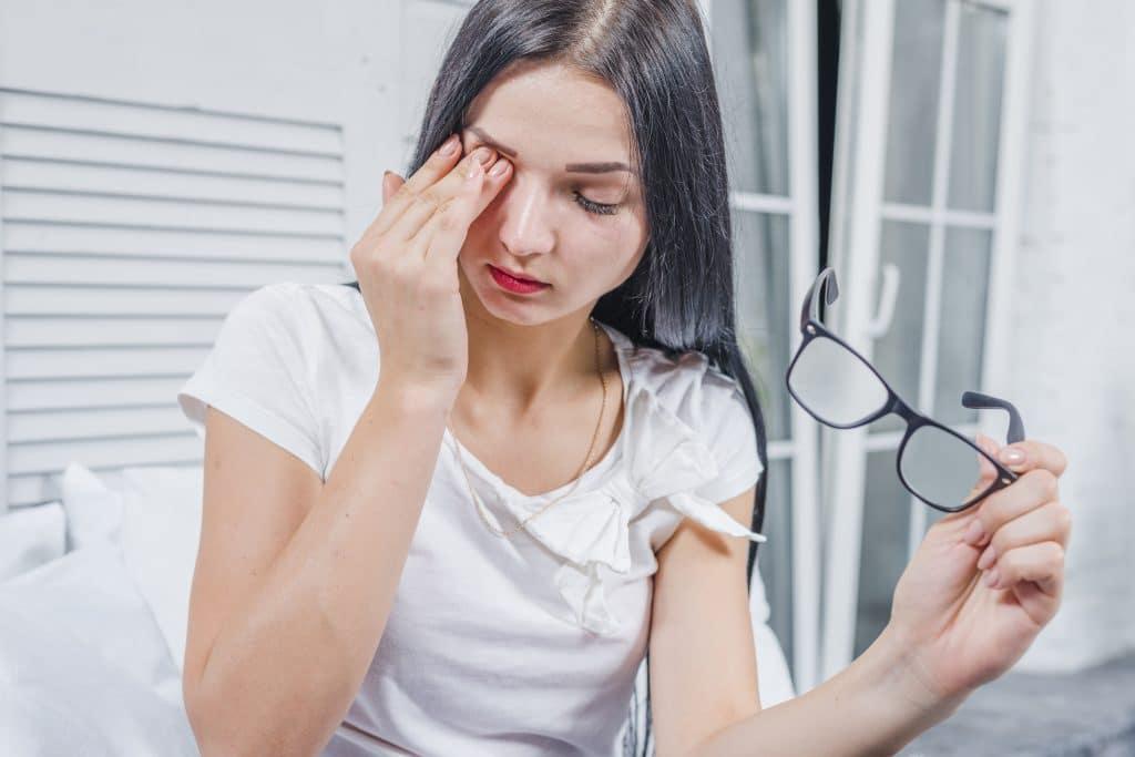 donna che si tocca occhio per dolore da congiuntivite allergica