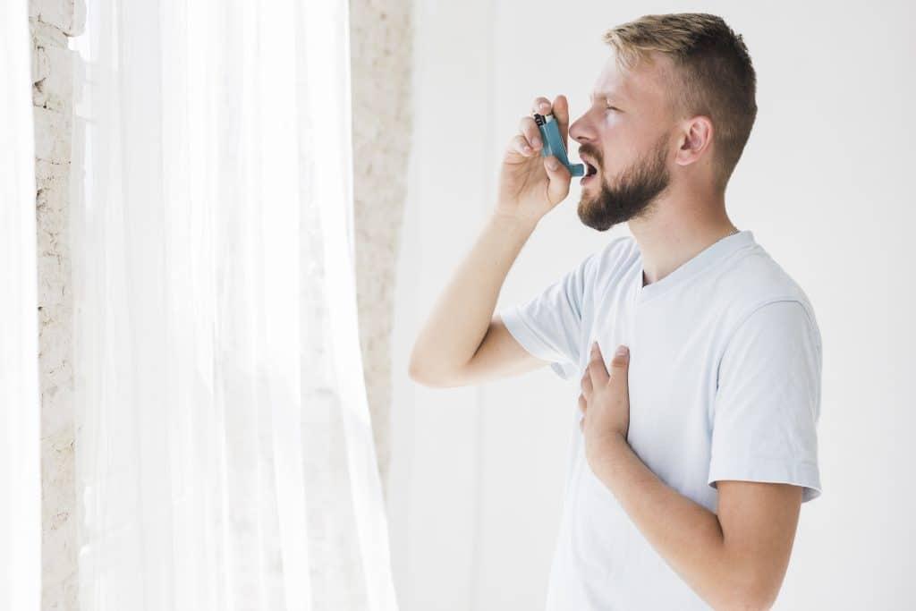 uomo con inalatore per asma