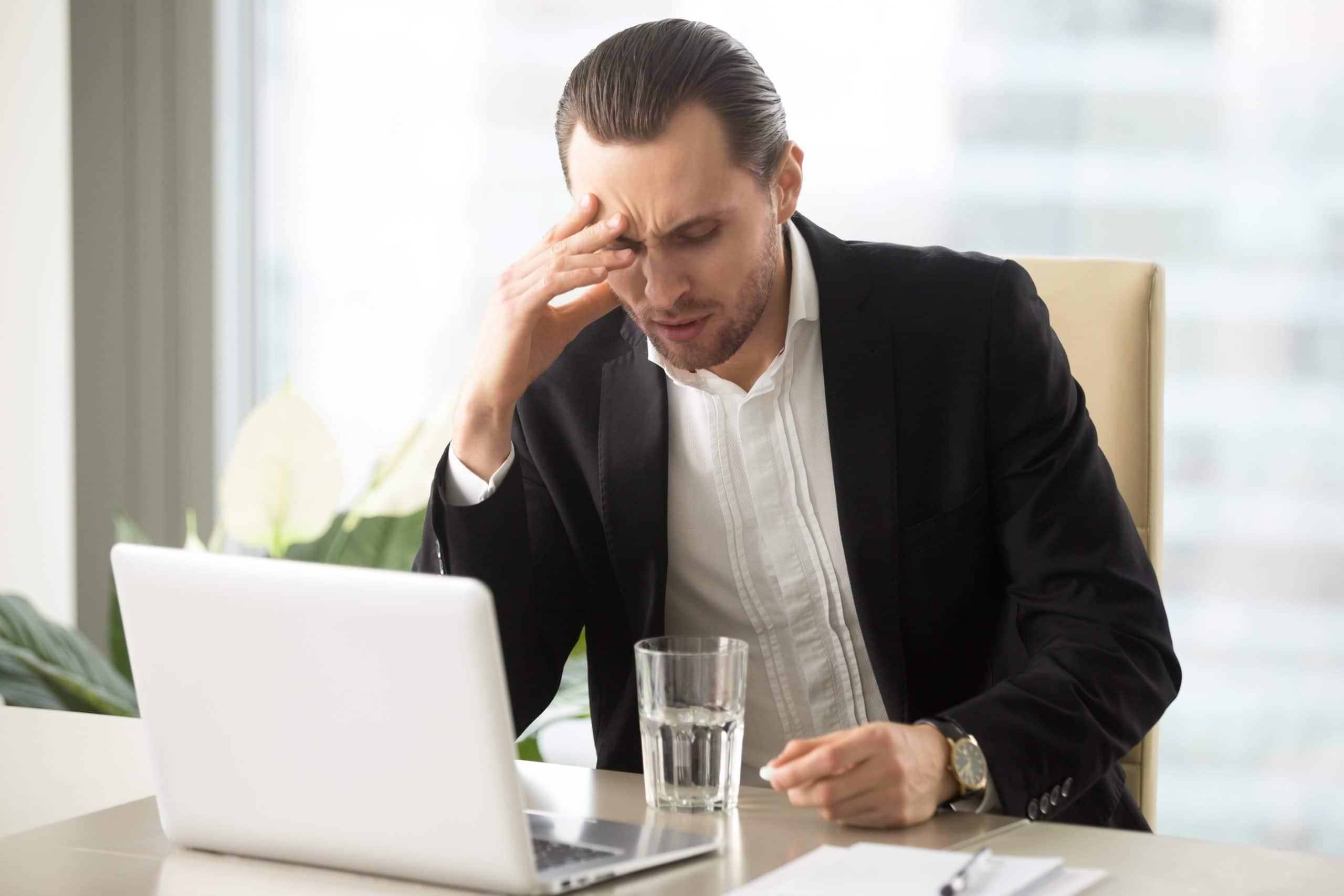 Uomo a lavoro davanti al computer che si tiene la testa, affetto da labirintite