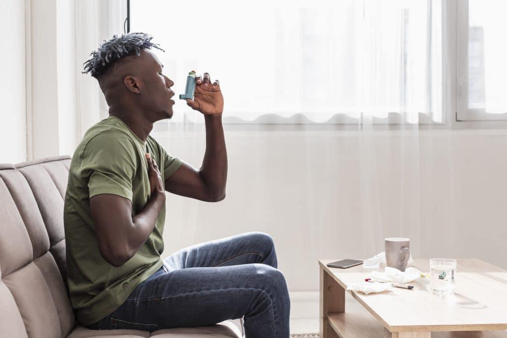 Uomo con respiro affannoso che usa inalatore per asma