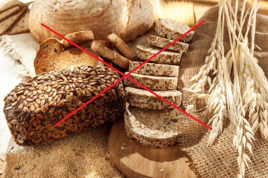 cos'è il glutine: tavola imbandita con cibi da evitare provenienti dal grano con grossa croce rossa sopra