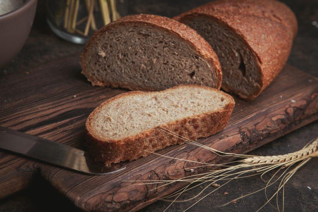 cos'è il glutine - Pane tagliato a fette su un tagliere di legno