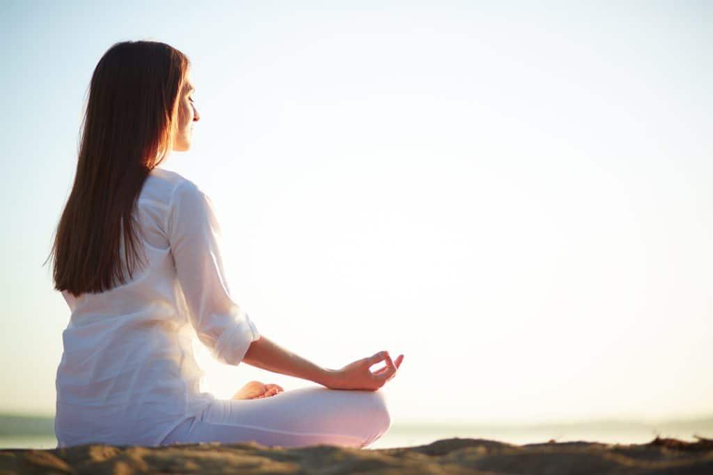 Donna che effettua esercizi di meditazione al tramonto per combattere ansia e perdita dei capelli