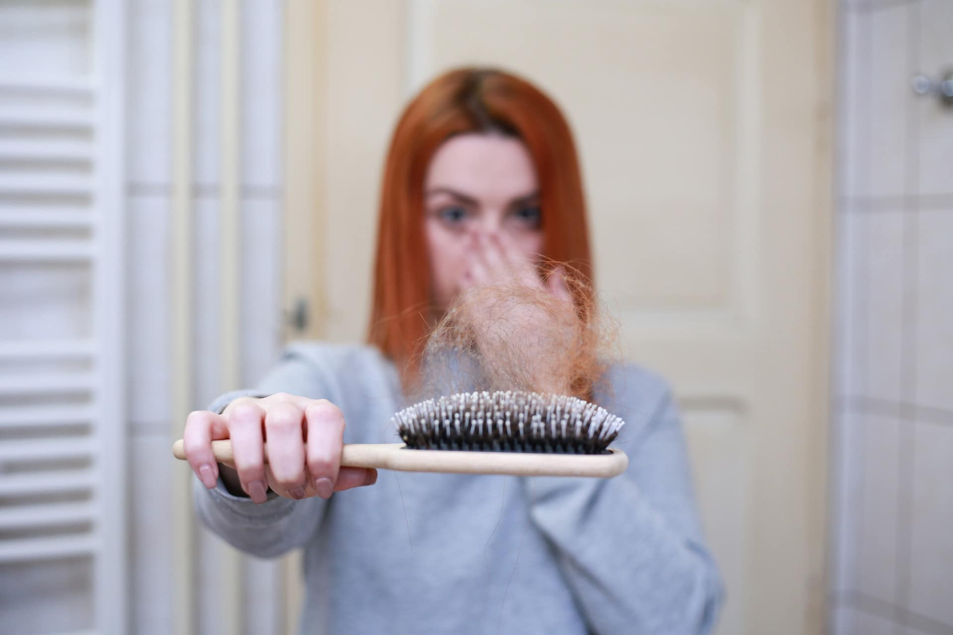 dpnna con perdita dei capelli che regge spazzola con tanti capelli attaccati