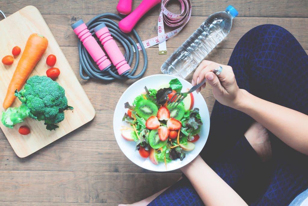 donna seduta che mangia cibo salutare  in una pausa dallo sport: prevenzione diabete parte da stile di vita sano