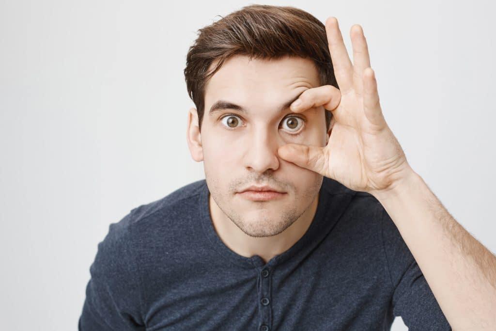 cataratta - uomo che si tocca occhio con la mano a mò' di occhiale