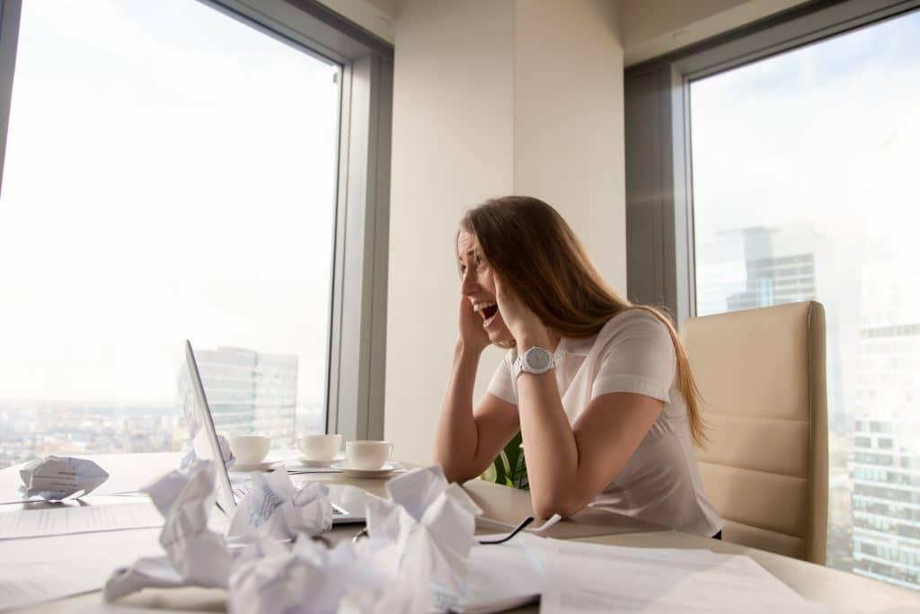 Donna a lavoro stressata che sta avendo un attacco di panico alla scrivania