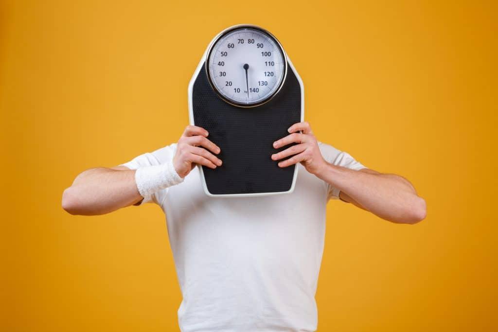 uomo che si nasconde dietro bilancia perché non riesce a perdere peso