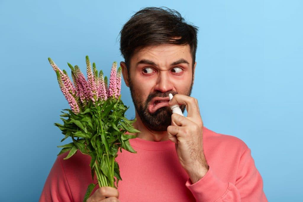 uomo con allergie di primavera con mazzo di fiori in mano