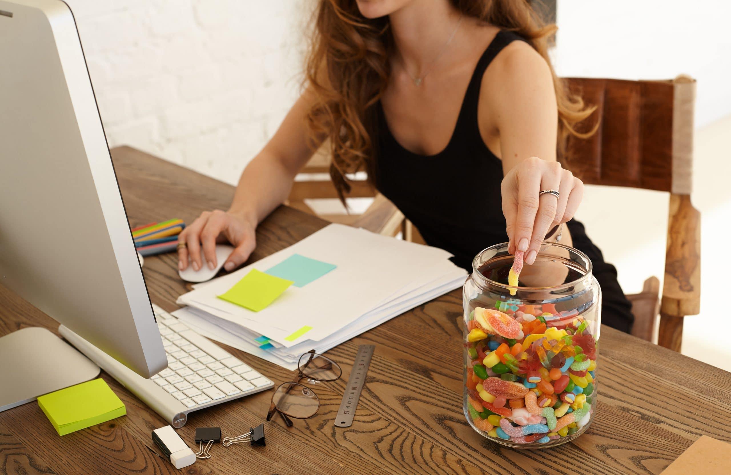 Donna che mangia caramelle davanti al computer